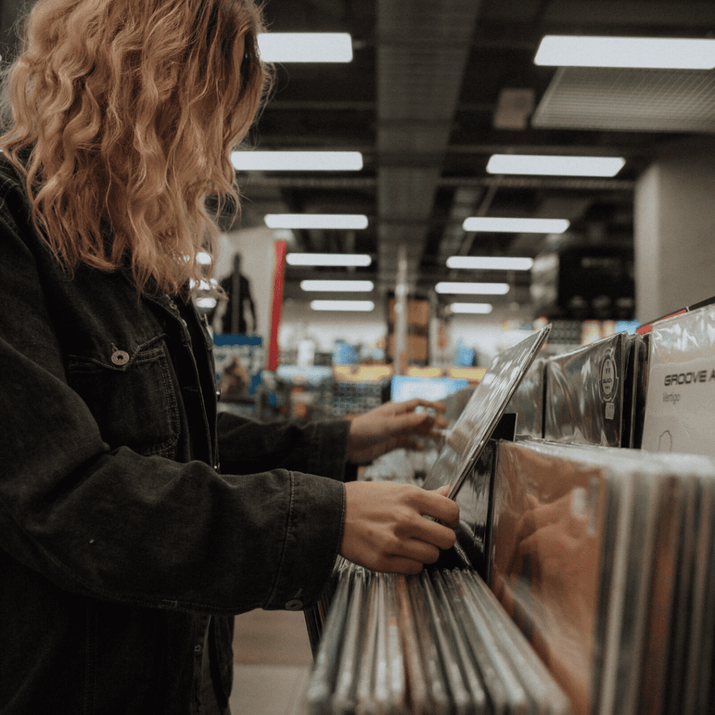 Woman in leather jacket browsing records at a record store